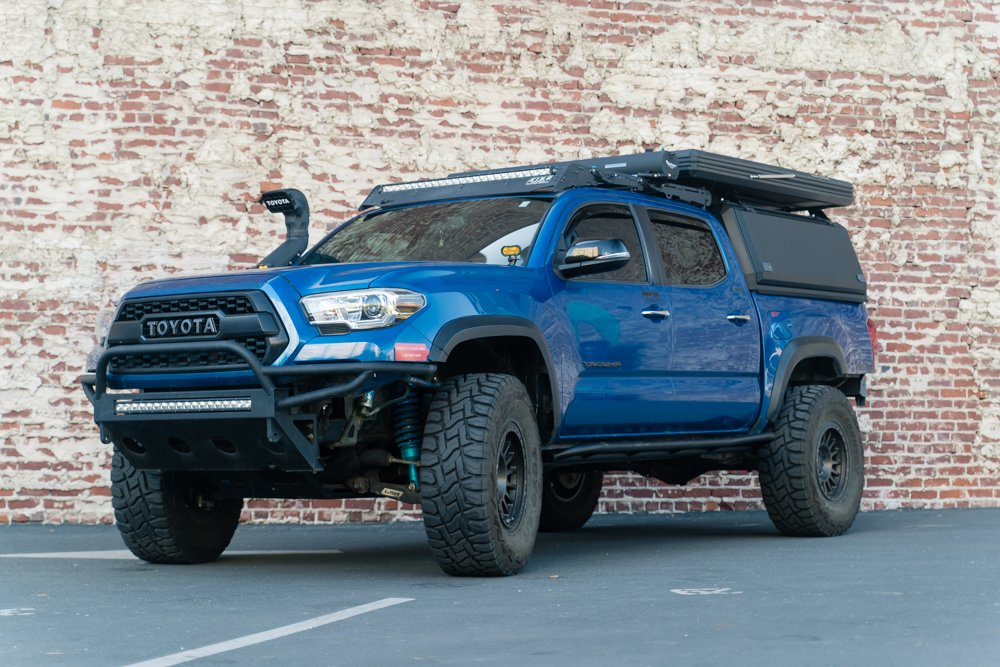 Lifted Blazing Blue Pearl Tacoma on 35 Inch Tires with AreaBFE Tent