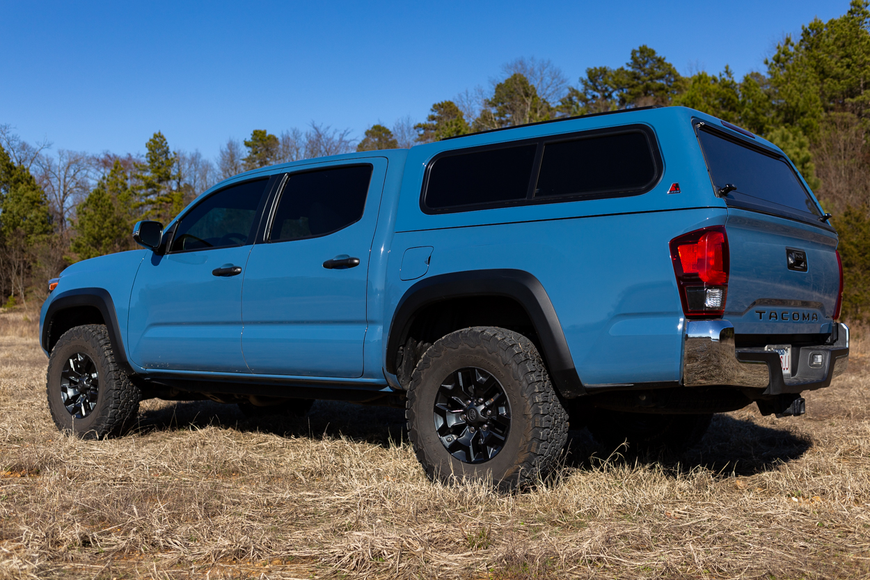 Cavalry Blue Toyota Tacoma with Fiberglass Leer Truck Cap & Black OEM Wheels