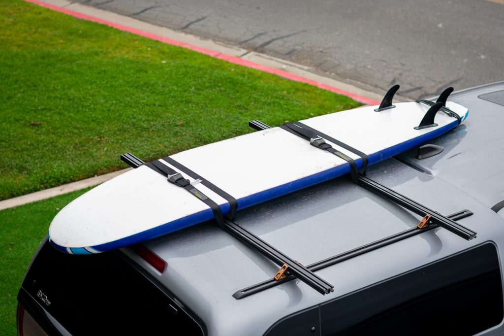 Surfboard Mounted to Custom Budget DIY Aluminum Roof Rack on Camper/Topper/Cap on 3rd Gen Tacoma