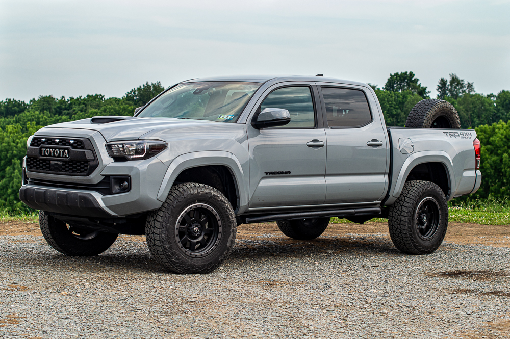 Lifted Cement 3rd Gen Toyota Tacoma with Mobtown Rock Sliders & Truck Bed Mounted Spare Tire Carrier